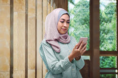 Pretty asian muslim woman with veil holding mobile phone Royalty Free Stock Photos