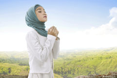 Pretty asian muslim woman wearing hijab raising hand and praying Stock Photos