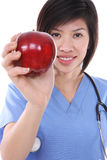 Pretty Asian Nurse with Apple Royalty Free Stock Photos