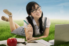 Pretty Asian schoolgirl studying at field Stock Image
