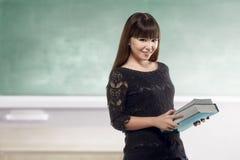 Pretty asian teacher holding book on class Stock Photos
