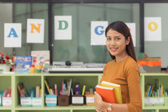 Pretty asian teacher smiling at camera at back of classroom at the elementary school. Vintage effect style pictures royalty free stock photos