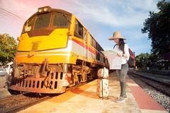 Pretty Asian traveler female looking map and waiting train. Royalty Free Stock Image