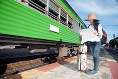 Pretty Asian traveler female looking map and waiting train. Royalty Free Stock Images