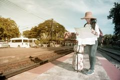 Pretty Asian traveler female looking map and waiting train. Stock Photo