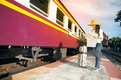 Pretty Asian traveler female looking map and waiting train. Stock Images