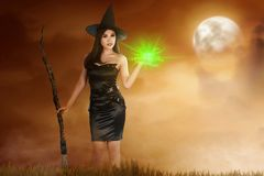 Pretty asian witch woman with broomstick and magic fire on her h stock image