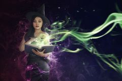 Pretty asian witch woman reading the incantation in book royalty free stock photography