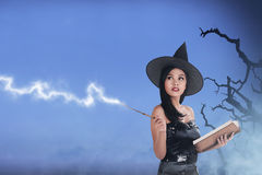 Pretty asian witch woman wearing hat and using her spell. With misty background royalty free stock images