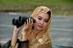 Pretty Asian woman with binoculars . Royalty Free Stock Image