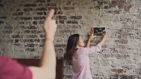 Pretty asian woman is choosing place for framed photograph on brick wall while her boyfriend is making frame shape with. His fingers and looking at her, male stock video footage