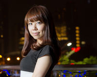 Pretty Asian woman with city light behind her Royalty Free Stock Photos