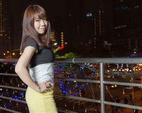 Pretty Asian woman with city light behind her Stock Image