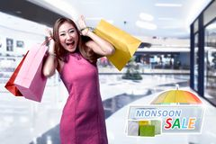 Pretty asian woman with colorful paper bag on the shopping mall. Monsoon sale concept Stock Photography