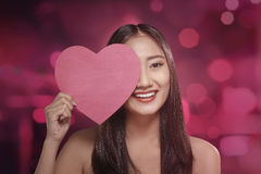 Pretty asian woman covering her eye with red heart symbol Stock Photography