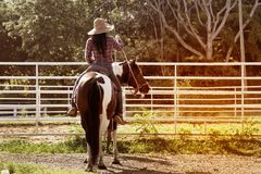 Pretty Asian woman cowgirl riding a horse outdoors in a farm. Royalty Free Stock Photography