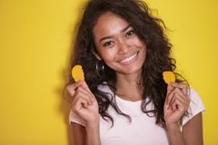 Pretty asian woman eating potato chips. Close up portrait of pretty asian woman eating potato chips on yellow background Royalty Free Stock Photos