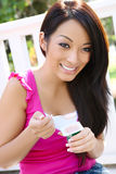 Pretty Asian Woman Eating Yogurt. A pretty asian woman at home eating yogurt Royalty Free Stock Photos