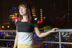 Pretty Asian woman in front of city lights royalty free stock images