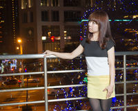 Pretty Asian woman in front of city lights stock photos