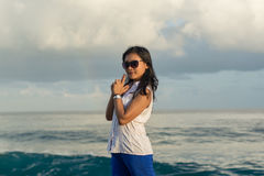 Pretty asian woman holding hands like a gun. At the sunset stock photos