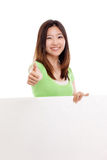 Pretty asian woman holding a penel and show thumb Stock Image