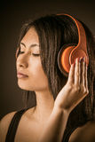 Pretty Asian woman listening to music Royalty Free Stock Photos