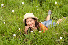 Pretty Asian woman lying on flower field. Royalty Free Stock Photography