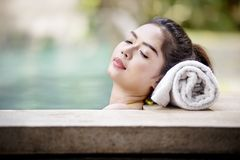 Pretty asian woman lying on the poolside. With white towel stock image