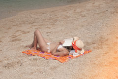 Pretty Asian woman lying relax on the beach. Royalty Free Stock Images