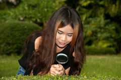 Pretty Asian woman with magnifying glass . Stock Photo