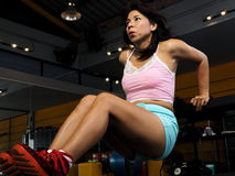 Pretty Asian woman performs bench dips at the gym Royalty Free Stock Images