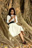 Pretty Asian woman on phone at old root tree . stock photo