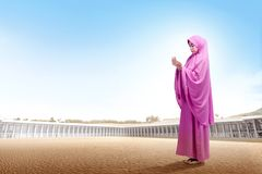 Pretty asian woman in pink veil standing on desert raise the hands and look down stock photo