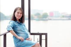 Pretty Asian woman is pregnant. Wearing a denim shirt Sit and relax in the garden. A pretty Asian woman is pregnant. Wearing a denim shirt Sit and relax in the stock image
