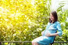 Pretty Asian woman is pregnant. Wearing a denim shirt Sit and relax in the garden. A pretty Asian woman is pregnant. Wearing a denim shirt Sit and relax in the royalty free stock photography