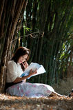 Pretty Asian woman reading a book . Stock Images