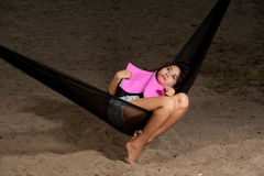 Pretty Asian woman reading a book lying in a hammock . Stock Photo