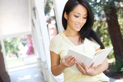 Pretty Asian Woman Reading at Home. A pretty asian woman at home reading on the porch Royalty Free Stock Image