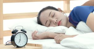Asian woman refusing to wake up lying on her bed. stock photo