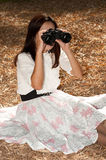 Pretty Asian woman seeking binoculars . Stock Photography