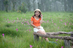 Pretty Asian woman sitting on flower field. Stock Photos