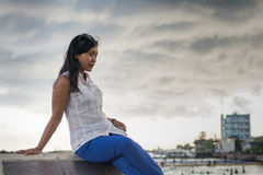 Pretty asian woman sitting under dark cloudy sky Stock Photography