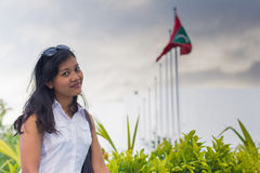 Pretty asian woman smiling and flag of Maldives at the background Stock Images
