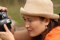Pretty Asian woman take a photo on flower field. Stock Photos
