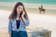 Pretty Asian woman is talking on mobile phone to communication. She is communicating with another people at Hua Hin beach in Prachuap Khiri Khan Province Royalty Free Stock Image