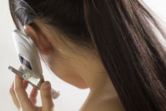 Pretty Asian woman using a cel. Close up view from behind of woman making  a cell phone call Stock Images