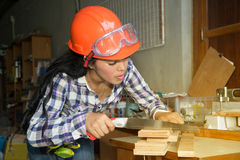 Pretty Asian woman using a hand saw to cut some wood. Royalty Free Stock Photos