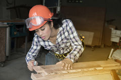 Pretty Asian woman using a hand saw to cut some wood. Stock Images