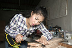 Pretty Asian woman using a hand saw to cut some wood. Stock Photos